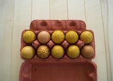 Ovos em um pacote em um fundo de madeira, isolado Os testes padrões amarelos são pintados Foto de Stock Royalty Free