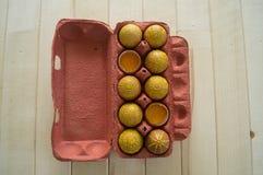 Ovos em um pacote em um fundo de madeira, isolado Os testes padrões amarelos são pintados Imagem de Stock