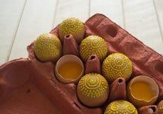 Ovos em um pacote em um fundo de madeira, isolado Os testes padrões amarelos são pintados Imagens de Stock