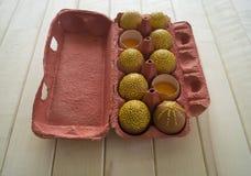 Ovos em um pacote em um fundo de madeira, isolado Os testes padrões amarelos são pintados Fotografia de Stock Royalty Free