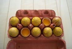 Ovos em um pacote em um fundo de madeira, isolado Os testes padrões amarelos são pintados Fotos de Stock