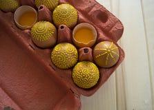 Ovos em um pacote em um fundo de madeira, isolado Os testes padrões amarelos são pintados Imagem de Stock Royalty Free