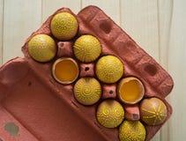 Ovos em um pacote em um fundo de madeira, isolado Os testes padrões amarelos são pintados Fotografia de Stock