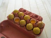 Ovos em um pacote em um fundo de madeira, isolado Os testes padrões amarelos são pintados Imagens de Stock Royalty Free