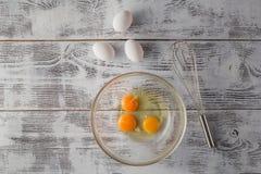 Ovos em uma bacia com batedor de ovos Imagem de Stock Royalty Free