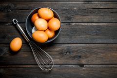 Ovos em uma bacia com um whisk imagem de stock royalty free