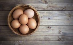 Ovos em uma bacia de madeira Fotografia de Stock Royalty Free