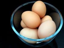 6 ovos em uma bacia de vidro, no preto Foto de Stock
