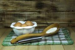 Ovos em uma bacia para a preparação da massa com farinha e misturador em um fundo de madeira rústico Imagem de Stock