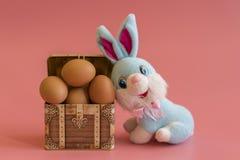 ovos em uma caixa e em um coelhinho da Páscoa Conceito da Páscoa no fundo cor-de-rosa foto de stock royalty free
