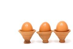 Ovos em uma cerâmica da argila no fundo branco Fotos de Stock