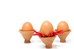 Ovos em uma cerâmica da argila no fundo branco Fotografia de Stock