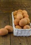 Ovos em uma cesta no fundo de madeira rústico Fotografia de Stock Royalty Free