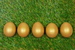 Ovos em uma grama artificial verde Fotos de Stock Royalty Free