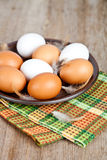 Ovos em uma placa, em uma toalha e em umas penas Fotos de Stock