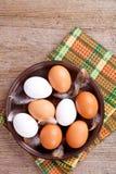 Ovos em uma placa, em uma toalha e em umas penas Foto de Stock Royalty Free