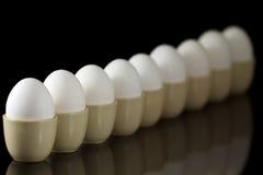 Ovos em uns egg-cups em uma fileira Fotografia de Stock Royalty Free