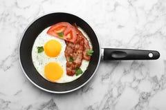 Ovos fritados do estrelado com tomate e bacon na bandeja no fundo de mármore foto de stock