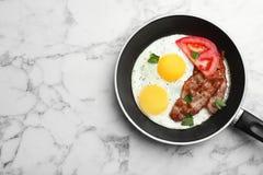 Ovos fritados do estrelado com tomate e bacon na bandeja no fundo de mármore, vista superior foto de stock