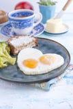 Ovos fritados sob a forma do coração Em uma placa escura com o copo azul dos brócolis e do brinde com chá, manteiga para o café d fotografia de stock royalty free