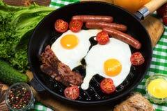Ovos fritos com bacon e salsichas em uma frigideira imagem de stock royalty free