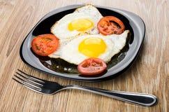 Ovos fritos com bacon e tomates na placa preta, forquilha Imagens de Stock