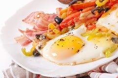 Ovos fritos com bacon, tomates, azeitonas e fatias de queijo Imagem de Stock