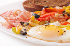 Ovos fritos com bacon, tomates, azeitonas e fatias de queijo Fotografia de Stock