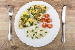 Ovos fritos com cogumelos e verdes, arroz, tomates na placa Imagens de Stock Royalty Free