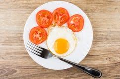 Ovos fritos com fatias de tomates na placa branca Fotografia de Stock