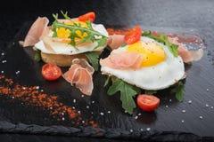 Ovos fritos com prosciutto e rúcula Foto de Stock