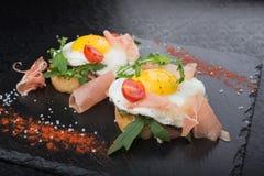 Ovos fritos com prosciutto e rúcula Fotos de Stock Royalty Free