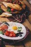 Ovos fritos com tomate, manjericão e prosciutto, grupo da tabela para o café da manhã acolhedor imagem de stock