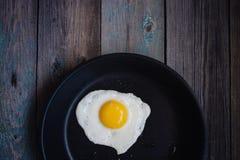 Ovos fritos da vista superior em uma frigideira em uma tabela de madeira foto de stock