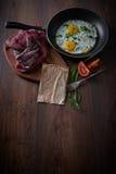 Ovos fritos em uma frigideira Com tomates e as cebolas verdes Em uma placa de corte, e em um fundo escuro Pequeno almoço saudável Fotos de Stock Royalty Free