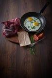 Ovos fritos em uma frigideira Com tomates e as cebolas verdes Em uma placa de corte, e em um fundo escuro Pequeno almoço saudável Imagens de Stock