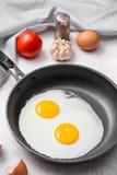 Ovos fritos em uma frigideira com tomates e pão de cereja para o Br Fotos de Stock Royalty Free