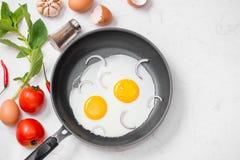 Ovos fritos em uma frigideira com tomates e pão de cereja para o Br Imagens de Stock