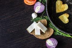 Ovos fritos na forma de um coração em uma frigideira, perto de que fatias do pão da configuração, salo da banha, cebola vermelha Imagens de Stock Royalty Free