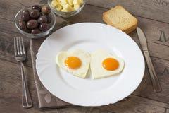 Ovos fritos na forma dos corações Imagens de Stock
