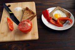 Ovos fritos no pão com os vegetais na tabela foto de stock royalty free