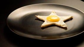 Ovos fritos numa forma de uma estrela em um prato Fotos de Stock