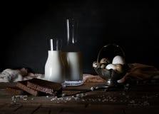 Ovos, leite e manteiga orgânicos frescos, ainda vida no estilo rústico, fundo de madeira do vintage Fotografia de Stock