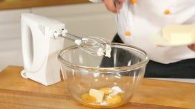 Ovos, manteiga e açúcar de mistura em uma bacia de vidro com um misturador filme