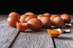 Ovos marrons da galinha fresca na madeira rústica no fundo preto Foto de Stock
