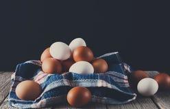 Ovos marrons da galinha fresca na madeira rústica no fundo preto, org Fotografia de Stock Royalty Free