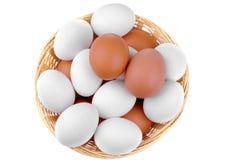 Ovos marrons e brancos de muita galinha em uma cesta de vime em um fundo branco Isolado Imagens de Stock