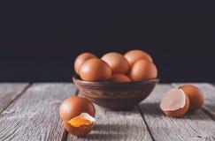 Ovos marrons frescos na bacia na madeira no fundo preto Fotos de Stock Royalty Free