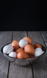 Ovos marrons frescos na bacia na madeira no fundo preto Imagens de Stock Royalty Free