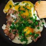 Ovos mexidos com bacon e cebolas no curso da preparação imagens de stock